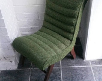 Vintage nursing chair with green fabric and wooden legs, soft cushioned original fabric