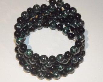 Bracelet of acrylic beads on memory wire, green and black, 4 wrap