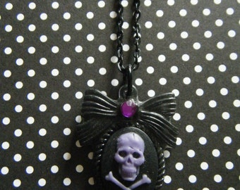 Purple skull on black embellished with purple rhinestone bow cameo necklace