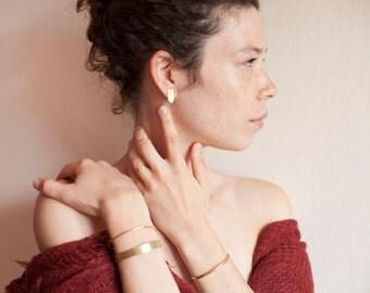 Stud earrings in brass, arrow shaped, geometrical simplicity. Ear stud is in silver