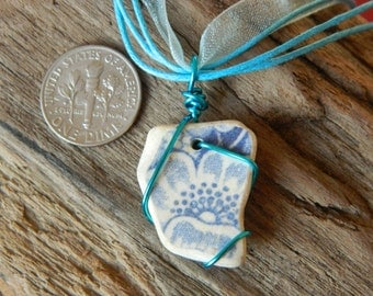 Beautiful wire wrapped sea pottery pendant with flower detail on a blue organza necklace