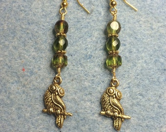Gold owl charm earrings adorned with olive green Czech glass beads.