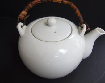 Vintage white porcelain teapot with bamboo handle