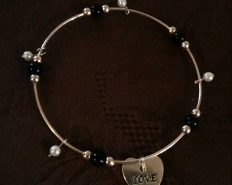 Loving silver bangle accented with pearls and black beads. Has Love dangle charm.