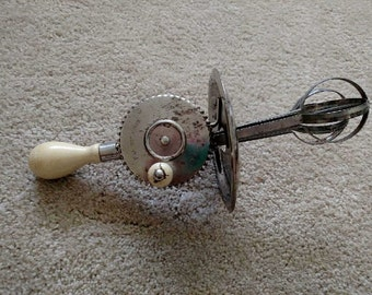 A&J hand mixer, egg beater with splash guard , cream colored wood handles, made in the USA. Patent October 9th 1923. Runs great