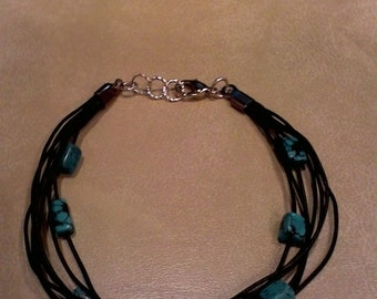 bracelet made of black or brown leather cord and tuquoise beads