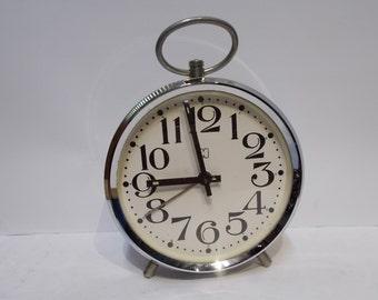 Vintage metal alarm clock with winding mechanism.