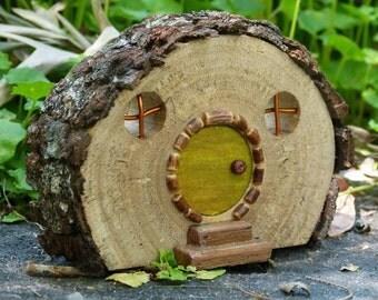 Rustic Wooden Hobbit house with Bark Roof and Green Door