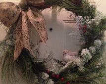 Rustic grapevine wreath with snowy evergreen boughs and tiny birdie