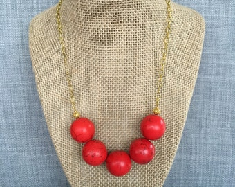Red beaded necklace on gold chain