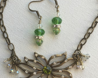 Beautiful womans flower necklace and earrings set, in antiqued brass metal with a green accent crystal.