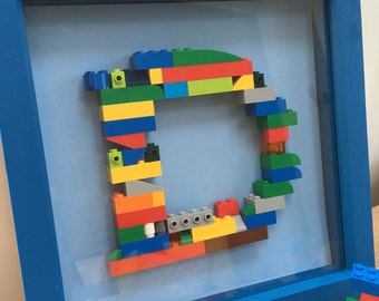 Building brick lego letter / initial in frame