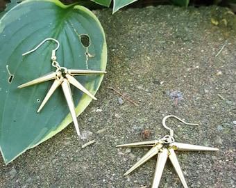 Gold spiked star dangle earrings