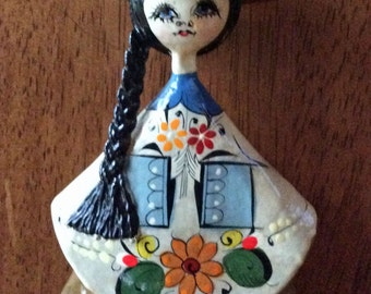 Whimsical vintage Mexican papier mache girl with black braid and serape