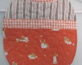Quilted reversible bib for baby/toddler girl with bunnies and flowers in pinks and orange