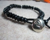 Black leather braided bracelet with Saki Silver button