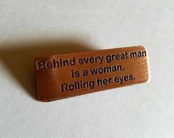Copper Pin - Behind every great man is a woman.  Rolling her eyes.