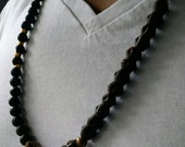 Makonnen Necklace (wood, lava beads, brass, red, gold, and green)