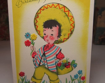 Colorful Buzza Cardozo 1940's-50's birthday card cute boy in sombrero and sarape gathering wildflowers in basket real plastic flower accents