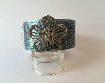 """Aqua finish faux leather cuff featuring rhinestone flower trim. 1 1/4"""" wide, measures 7 3/4"""" from snap to snap"""