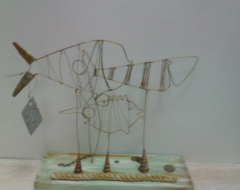 Decorative fish from the wire on a wooden stand.