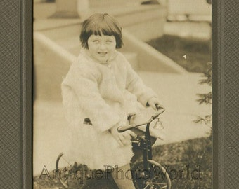 Cute girl on iron tricycle bicycle antique photo