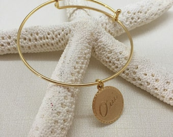 Gold plated adjustable  bangle with french charm.