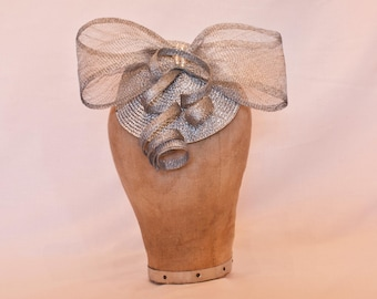 Silver fascinator hat with bow and coil detailing.