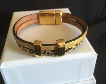 leather strap prints black and gold buckle and clasp flashed gold