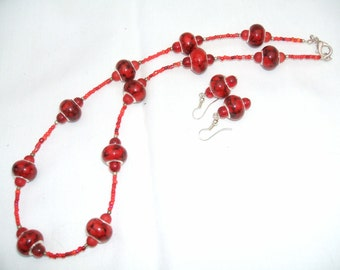 Red charm style beaded necklace and matching earrings.