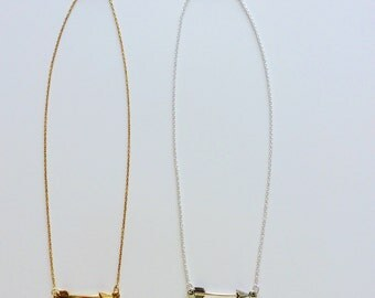 Silver chain necklace with silver arrow . Gold chain necklace with gold arrow .