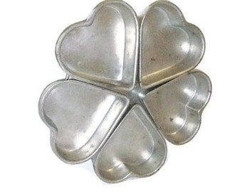 Five Heart Tart Tins Attached To A Base