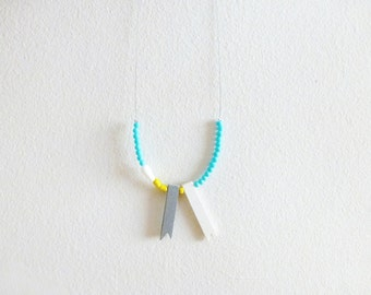 geometric asymmetrical tribal necklace with yellow sticks and white beads, contemporary jewelry