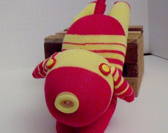 Sock Dog With Long Ears and Button Eyes and Nose Made from a Yellow and Striped Red Sock laying Down and Has Cute Red Pose-able Red Tail