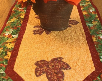 Handmade quilted fall table runner with appliqued fall leaves in autumn colors