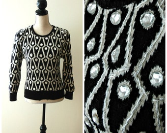 Vintage black and white geometric angora blend sweater with rhinestone embellishments and puff shoulder.