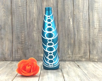 Blue metallic painted bottle with white geometric pattern