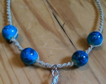 Wire wrapped citrine gemstone on a spiral knotted hemp necklace with blue decorative beads