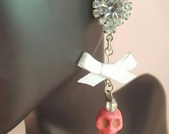Rhinestone earrings featuring a white bow and pink skull
