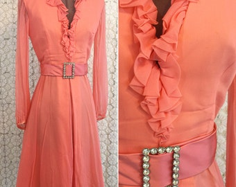 Beautiful coral taffeta dress with sheer overlay, taffeta belt with rhinestone buckle, snap down at end. Gathered elastic cuffs, mid length