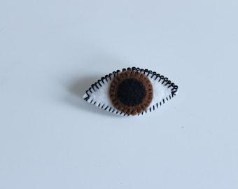Dark brown seeing eye brooch