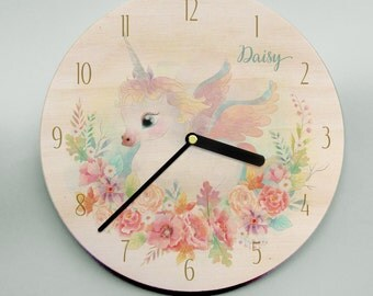 Child's name clock with unicorn and flowers in pastel pinks, blues, greens and purples on wooden clockface