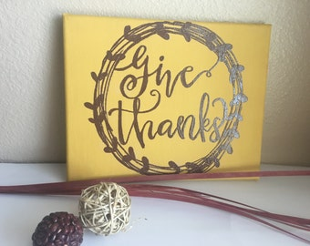 Embossed brown letters on mustard colored fall canvas
