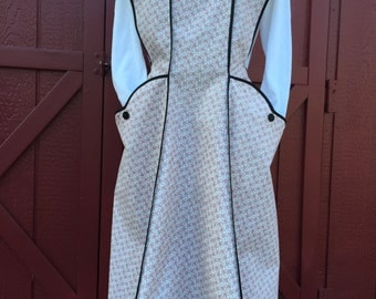 Retro But Trendy Full Apron. Full apron with generous fit and large pockets, done in a quality cream print 100% cotton and trimmed in black.