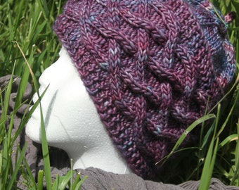 Purple hat with cables knitted hand