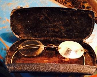 Antique brass rimmed glasses in case with velvet lining