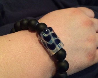 Black beads with a amazing hand made glass bead with streaks of blue in it