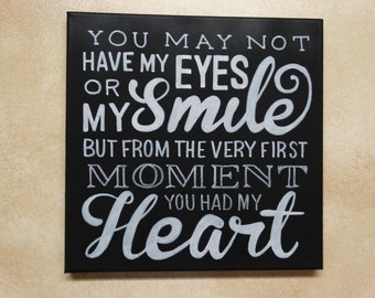 "Black canvas sign ""You may not have my eyes or my smile but from the very first moment you had my heart"""