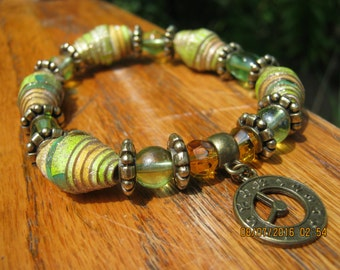 Stretch handcrafted bracelet with shades of peach, green, and glitter