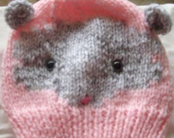 Pink knitted hat with ferret on